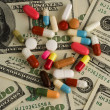 Pills of different colors on money background. - Stock Photo
