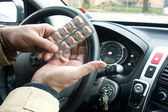 Driver holding pills in hand — Stock Photo