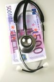 Stethoscope with pile of money — Stock Photo