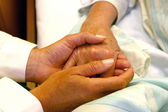 Doctor holding hands of patient — Stockfoto