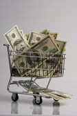 Shopping basket with dollar bills — Stock Photo