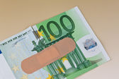 Euro bank notes with adhesive plaster — Stock Photo