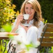 Woman drinking coffee at breakfast in the garden - Stock Photo