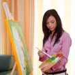 Young girl painting on an easel — Stock Photo #8626428