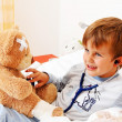 Sick child teddy examined - Stock Photo