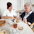 Nurse helps elderly woman at breakfast — Stock Photo