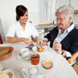 Nurse helps elderly woman at breakfast — Stock Photo #8626900