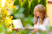 Woman with laptop in the garden — Stock Photo