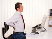 Man in office with back pain — Stock Photo