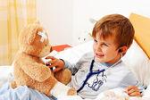 Sick child teddy examined — Stock Photo