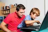 Man and child with laptop — Stock Photo