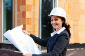 Architect with plan on construction site — Stockfoto
