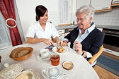 Nurse helps elderly woman at breakfast — Стоковое фото