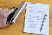 Abnschiedsbrief and gun — Stock Photo