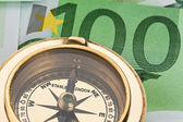 Euro banknote with a compass — Stock Photo