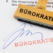 Wooden stamp on the document: bureaucracy — Stock Photo
