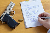 Letter and the gun of a suicide. — Stock Photo