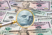 Dollar currency notes photographed with a magnifying glass — Stock Photo