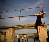 Girl on the ruins of the pier — Stock Photo