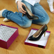 Girl gets black shoes out of box. — Stock Photo #8081225