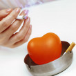 Orange heart in  ashtray and a woman's hand with a cigarette. — Stock Photo