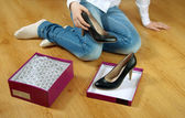 Girl gets black shoes out of the box. — Stock Photo