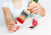 Girl paints nails with the big brush. — Stock Photo