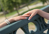 Two woman's hand quietly lay on the handrail. — Stock Photo