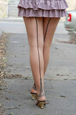Women's slender legs in stockings and a skirt on the street. — Stock Photo