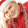 Stock Photo: Smiling young man in a red shirt, hat Santa Claus and tinsel in