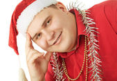 Smiling young man in a red shirt, hat Santa Claus and tinsel in — Stock Photo