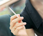 Cigarette smoking in women's hand. — Stock Photo