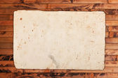 Faded old paper on wood — Stock Photo
