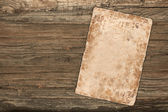 Old empty paper on a wooden background — Stock Photo