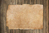 Weathered dark paper on wood — Foto Stock