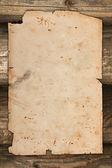 Papel viejo dañado en un fondo de madera — Foto de Stock