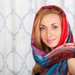 Smiling young woman in a colorful scarf — Stock fotografie