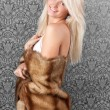 Beautiful blond girl in white bikini and fur coat — Stock Photo #8417061