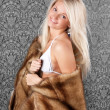 Lovely blond girl in white bikini and a fur coat — Stock Photo #8417179