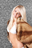 Pretty blond girl in white bikini and a fur coat — Stock Photo
