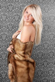 Beautiful blond girl in white bikini and a fur coat — Stock Photo
