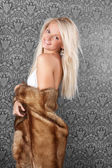Gorgeous young blond girl in a fur coat — Stock Photo
