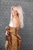Attractive blond girl in white bikini and a fur coat — Stock Photo
