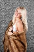 Lovely blond girl in white bikini and a fur coat — Stock Photo