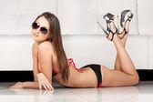 Sexy brunette fashion model in dark bikini and sun glasses — Stock Photo