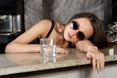 Beautiful brunette girl in sun glasses with a glass of vodka — Stock Photo