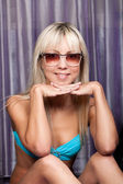 Gorgeous blond girl in blue bikini and sun glasses — Stock Photo