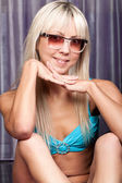 Gorgeous smiling blond girl in stylish blue bikini — Stock Photo