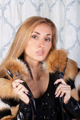 Sensual brunette model in a stylish fur coat — Stock Photo