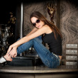 Royalty-Free Stock Photo: Hot and stylish brunette in sun glasses on a bar table
